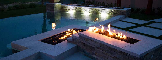 two fire pits around outdoor pool at night-Five Fire Features to Brighten Any Home-Richardson Custom Homes-Fort Myers–615x230jpg